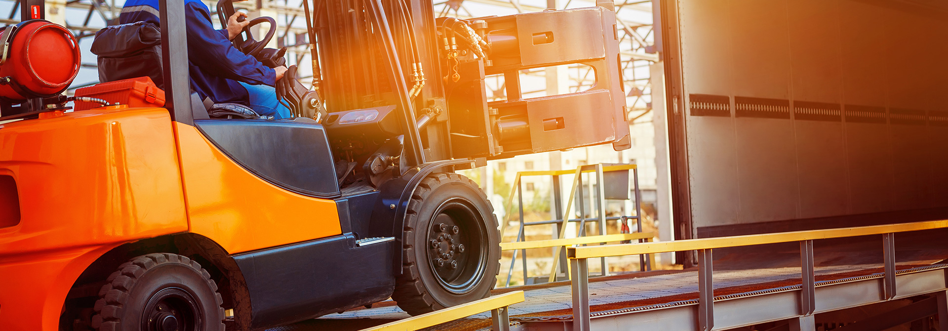 Man using heavy machinery to load a truck with supplies | Virginia Defective Machinery Attorneys